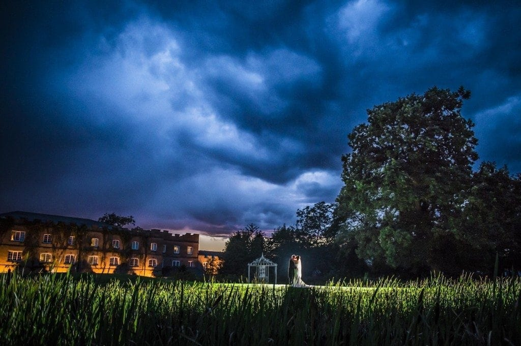 a gorgeous night shot of vicky & martin in front of the ramside hall hotel with a storm sky